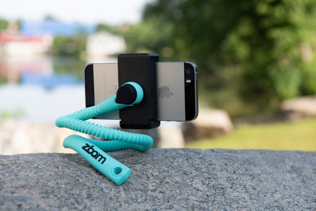 A teal Gekkostick flexible phone holder sits perched on a rock poised to take a photo