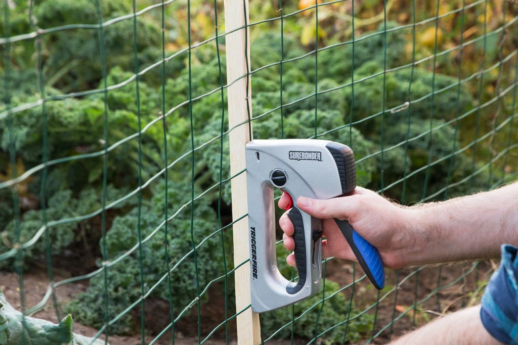 A man staples wire fencing to a garden using TriggerFire's kickback-free staple gun