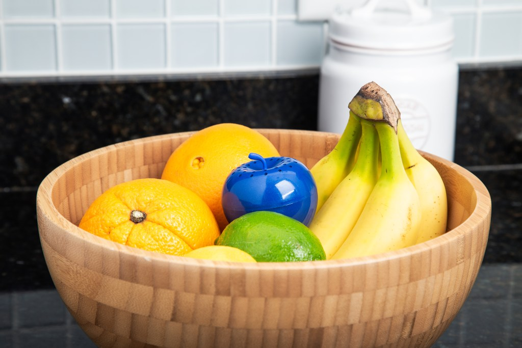 A wooden bowl filled with fruit sits on a counter, a BluApple produce preserver soaks up the ethylene gas