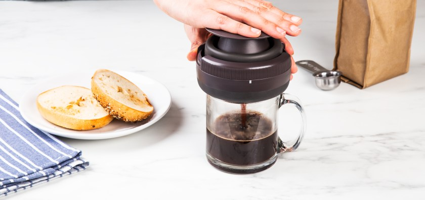 A person presses fresh coffee with Palmpress on a counter next to their breakfast