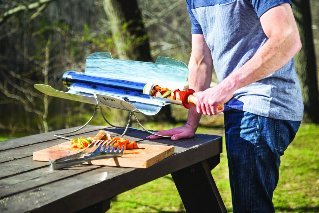 A man harnesses the power of the sun to cook skewers with GoSun's solar cooker