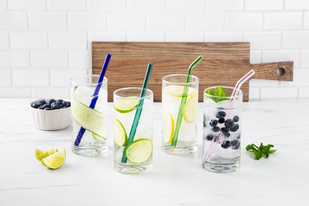 4 iced drinks sit on a counter with multicolored reusable glass straws from Strawesome