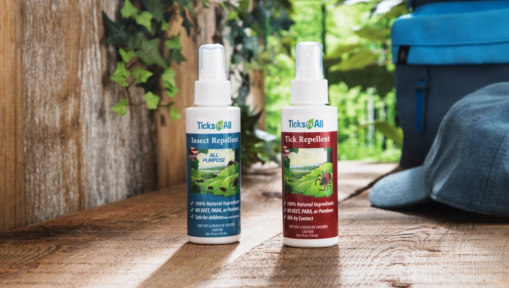 Tick & Insect repellant spray bottles from Ticks-N-All sit on a wood patio