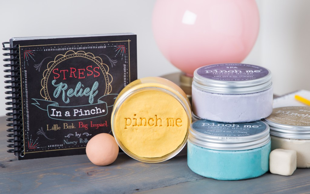 Several jars of pinch me therapy dough sit next to a stress relief book