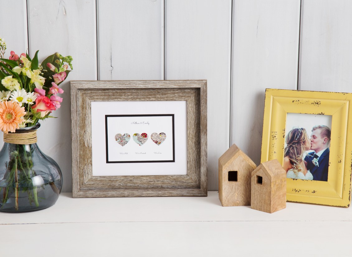 Nathan & Emily's Paper'd Moments love map story art sits on a shelf with their wedding photos