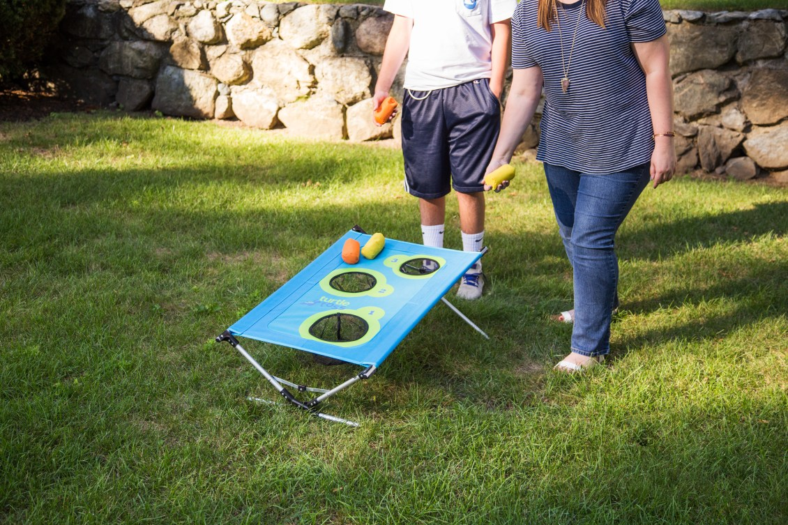 A pair gets ready to toss a bean bag to score at TurtleToss