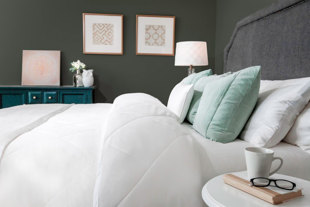 A cozy bedroom shows white and mint colored bamboo fiber bedding from Cozy Earth
