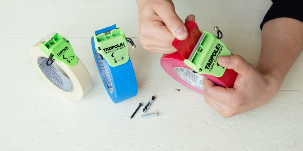 A person uses TadPole tape cutter to perfect cut red duct tape, blue painter's tape & masking tape