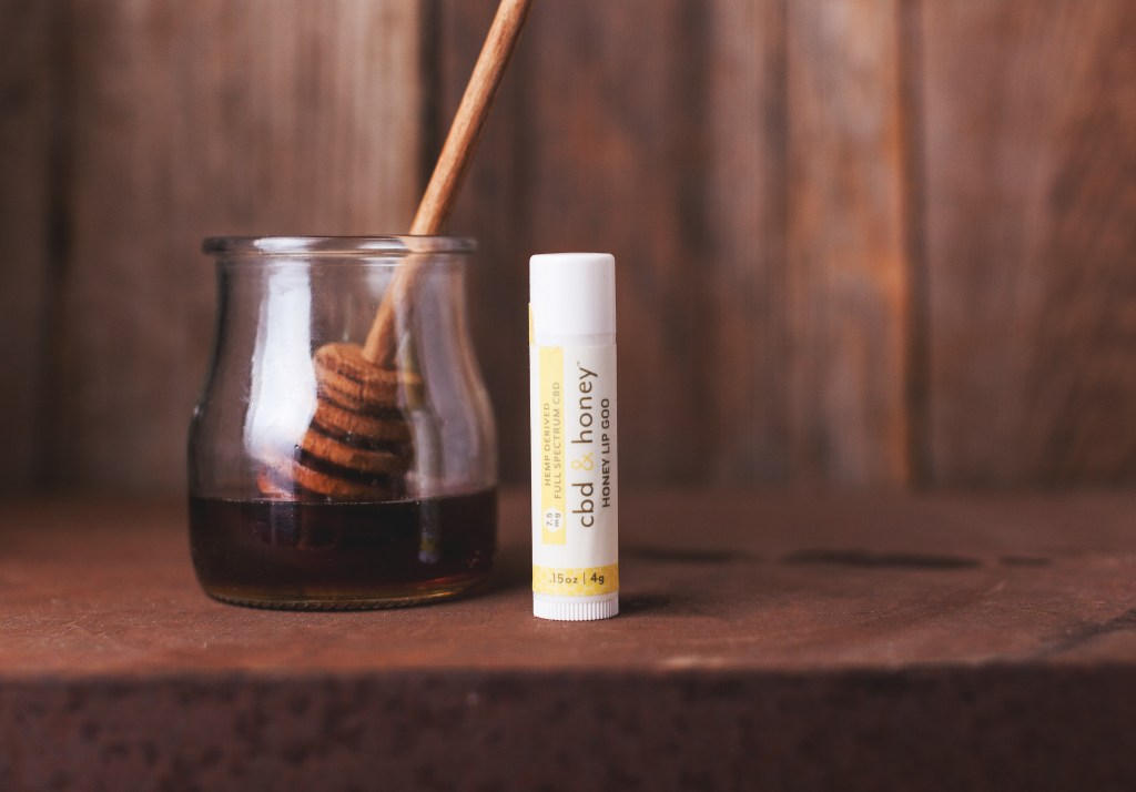 A stick of Life Elements' CBD & honey lip balm sits on a table next to a jar of honey