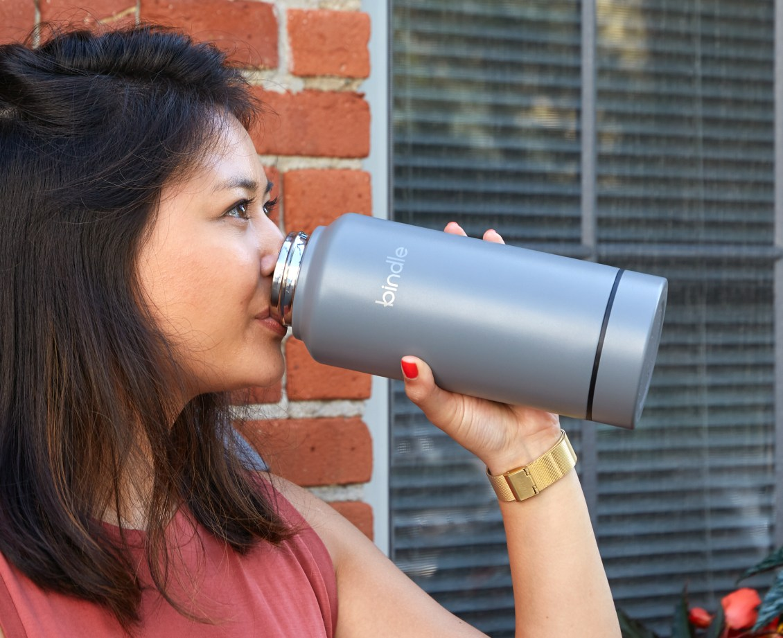 A woman can be seen drinking from a gray Bindle Bottle