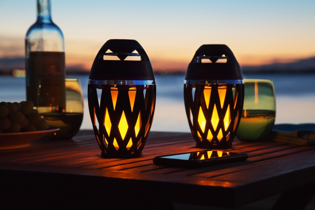 Two Tiki Tunes LED Speakers On a table at sunset