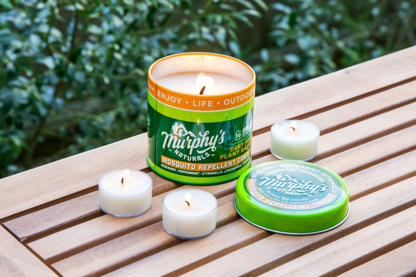 One large mosquito repellant candle and three small mosquito repellant tealights from Murphy's Naturals are lit on top of a table