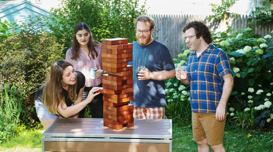 Four people playing Tumbling Timbers on top of a table