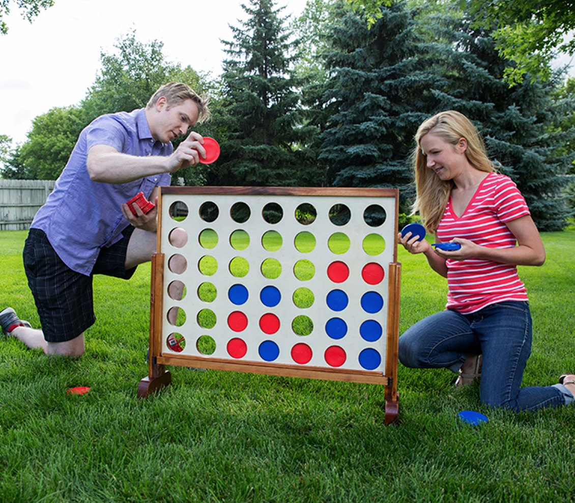Two people playing 4 Connect on a lawn