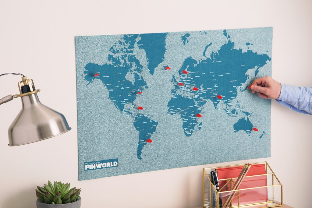 A man places a pin on his blue Palomar felt world map to mark his travels