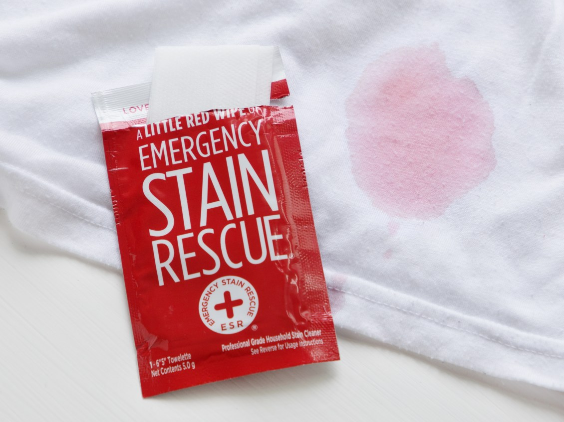 A little red wipe of emergency stain rescue sits next to a white shirt stained with red wine