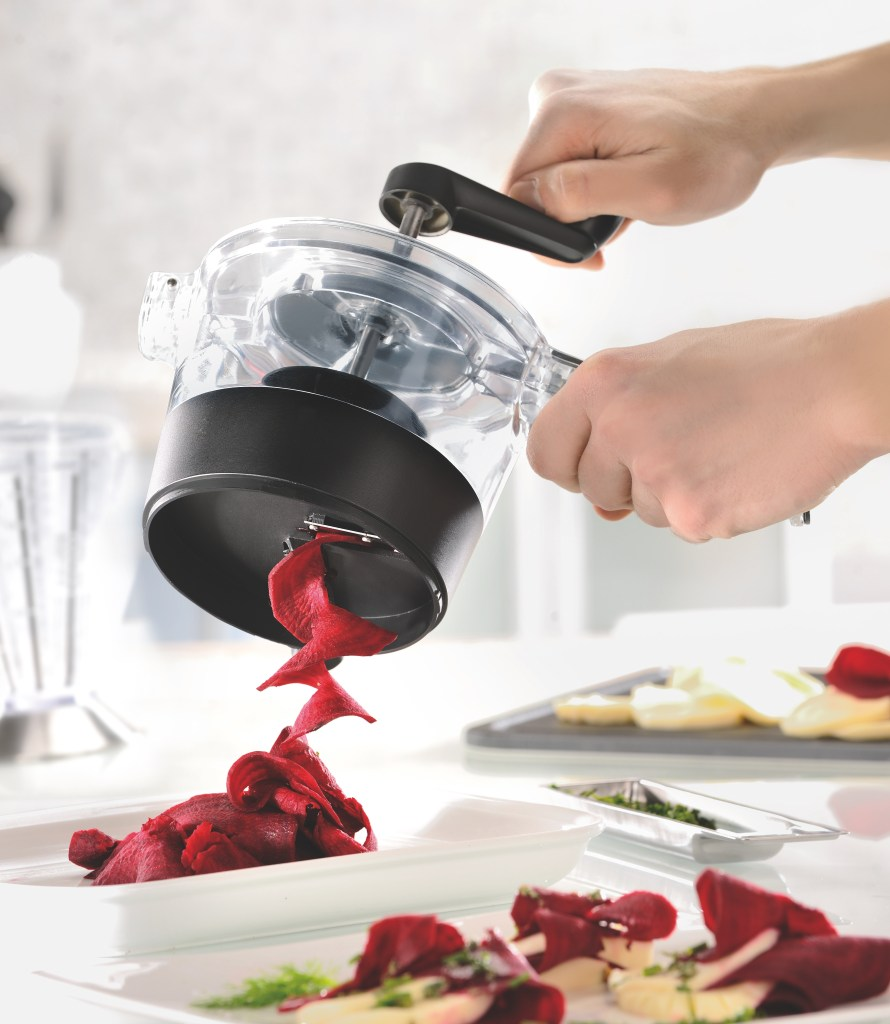 A person is seen spiralizing thick ribbons of beets with a Spirelli spiralizer