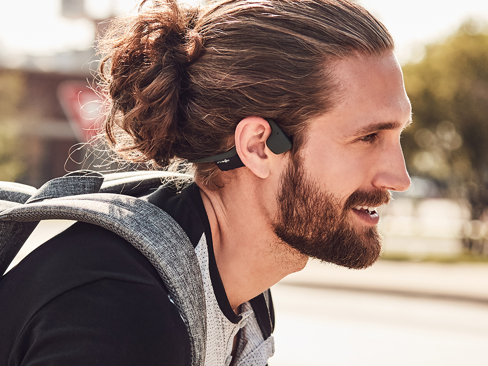 A man is seen wearing AfterShokz Trekz air headphones