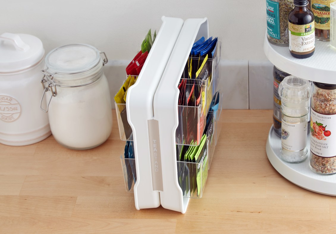 Tea bags are nearly organized on a counter with YouCopia's TeaStand tea bag organizer