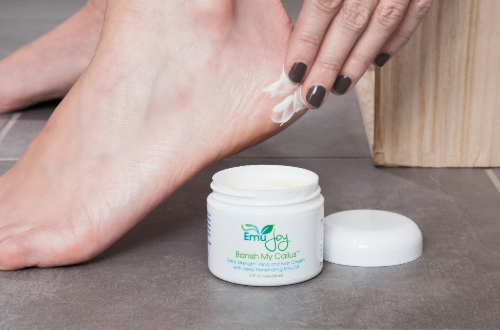 A woman is seen rubbing Emu joy's Banish My Callus foot cream on her heels