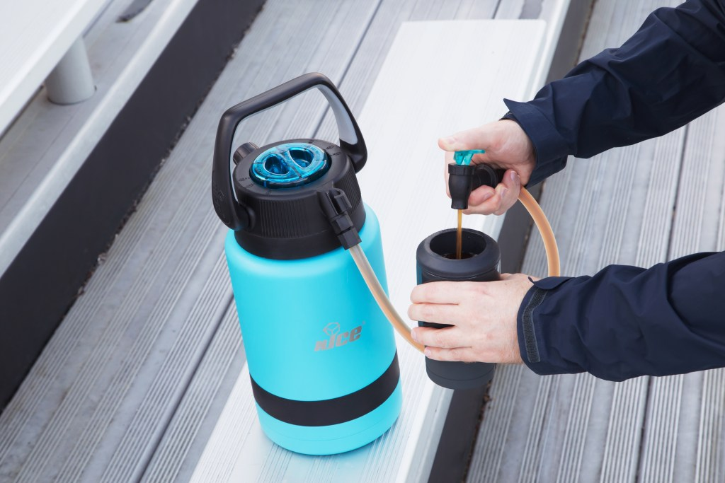 A person pours a drink out of a teal n'ICE Cooler Pump2Pour insulated jug