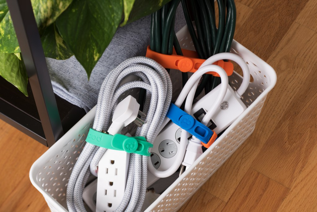 Extension cords & power strips sit in a bin, their cords wrapped up & organized using Packbands silicone bands