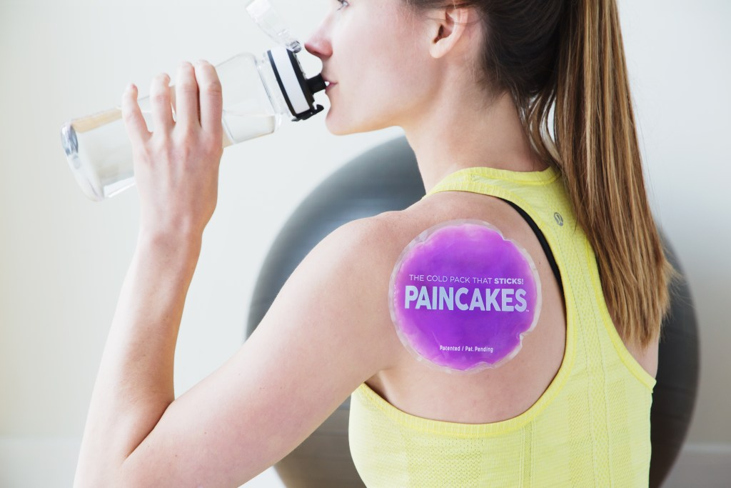 A woman is seen drinking water with a purple Paincakes adhesive cold pack on her shoulder