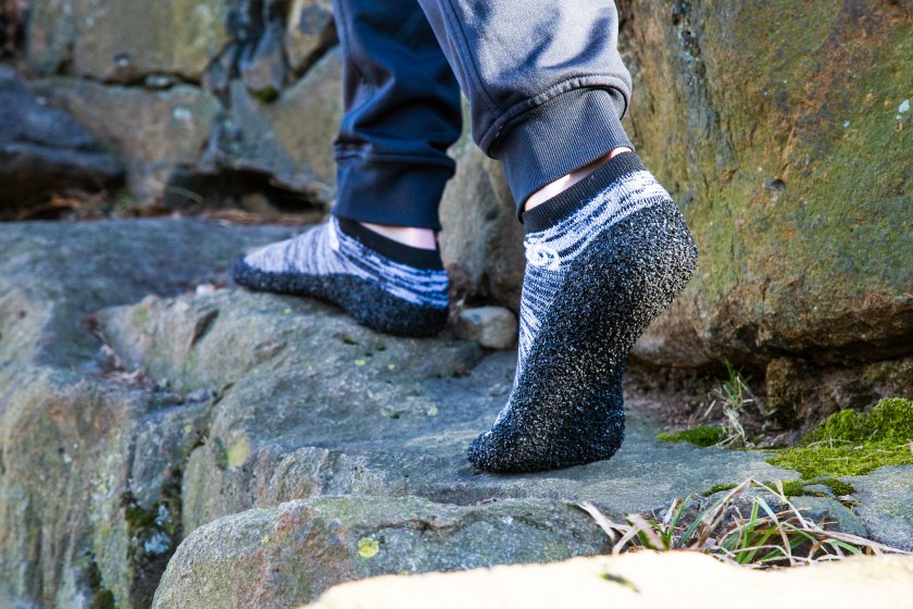 A person walks along a rock edge wearing black & gray barefoot sock shoes from SKINNERS