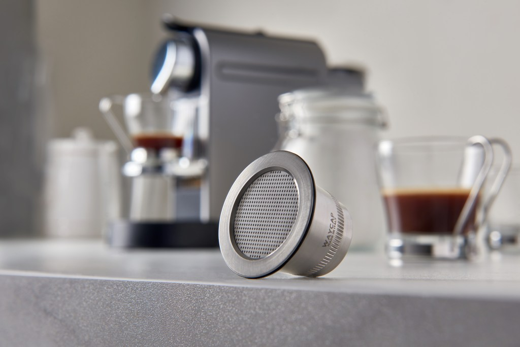 shots of fresh espresso are seen next to a stainless steel Nespresso capsule from WayCap
