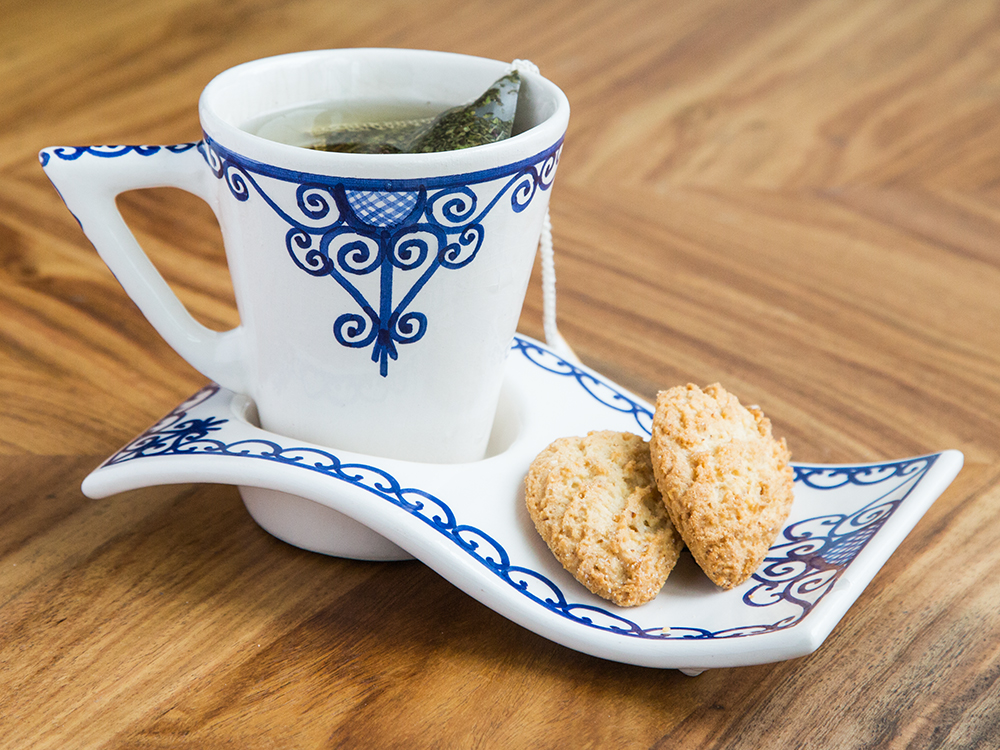 Tea & cookies sit in a beautifully decorated mug & coaster set from Kamsah