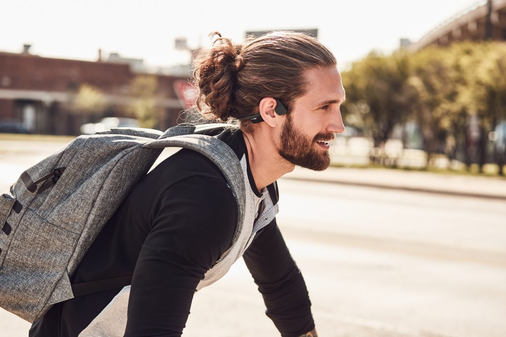 A man is seen wearing AfterShokz Trekz air headphones while riding a bike