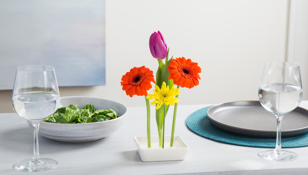 Bright single-stemmed flowers stand tall in a floating vase from Florida Vase