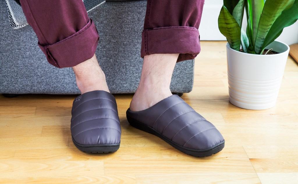 A man is seen sitting wearing grey SUBU indoor/outdoor slippers