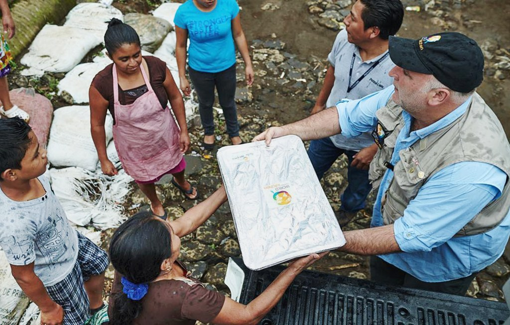 World Central Kitchen volunteers are seen handing trays of food to a community devastated by hurricanes