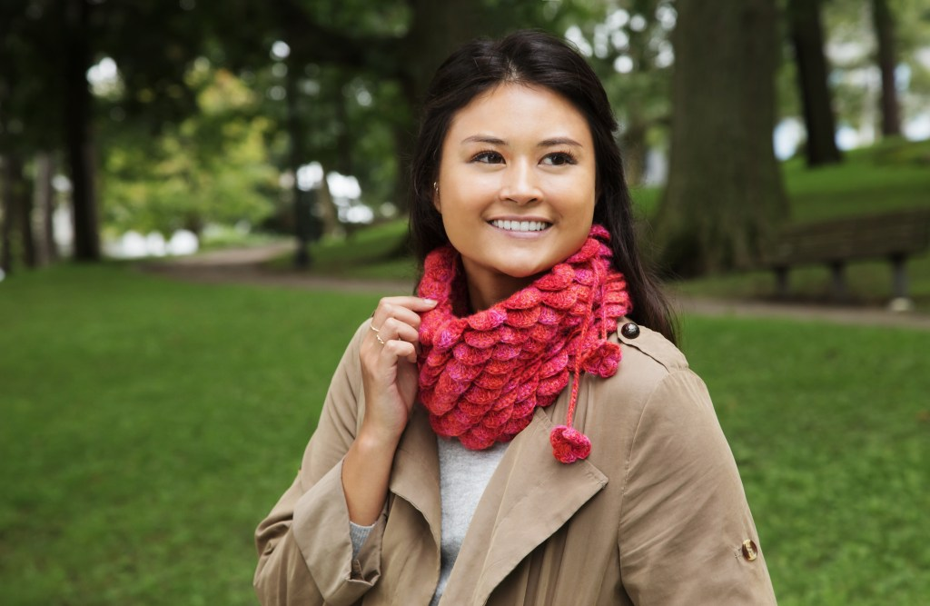 A woman is seen in a park wearing a pink scalloped neck warmer from Peruvian Trading Company
