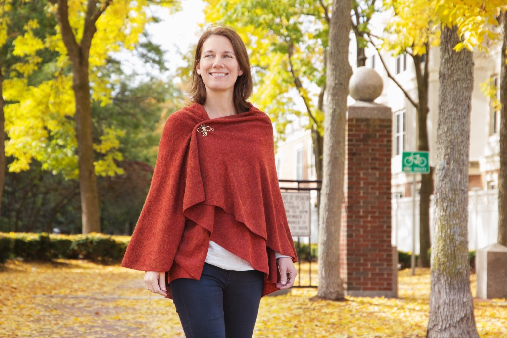 A woman is seen walking in a park in autumn wearing a burnt orange multi-wrap shawl from Demdaco