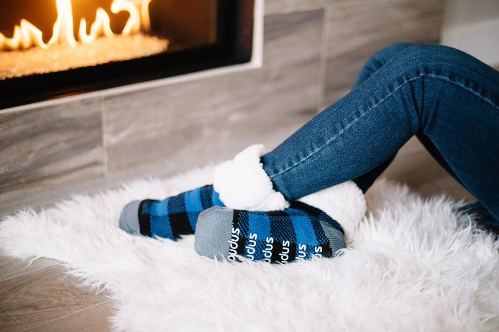 A woman's legs are seen lounging by the fire, with blue PUDUS slipper socks on her feet