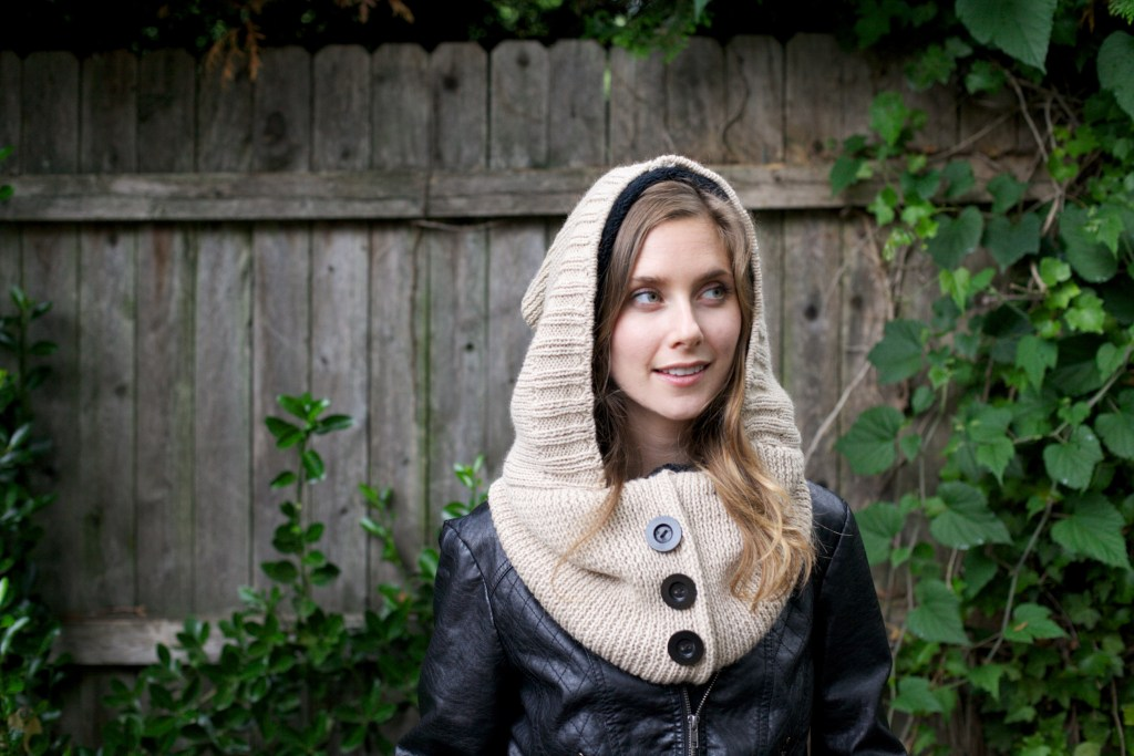 A woman is seen in a yard wearing a cream colored lined Alpaca hooded scarf from Wild Mantle