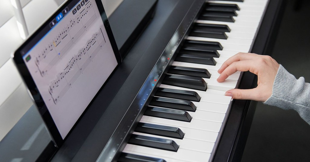 A person is seen using their tablet to help compose music on their One Music Group piano