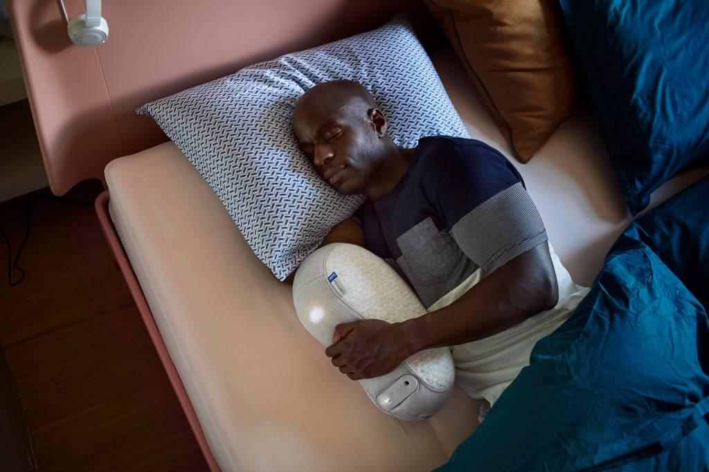A man is seen sleeping in bed, snuggling his Somnox rhythmic breathing sleep machine