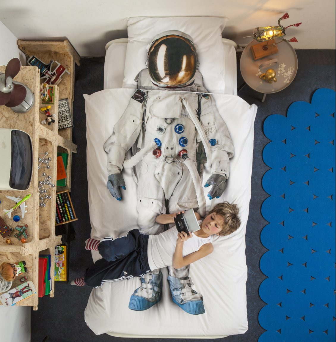 A little boy is seen laying on his bed covered by an Astronaut duvet cover from Snurk Living
