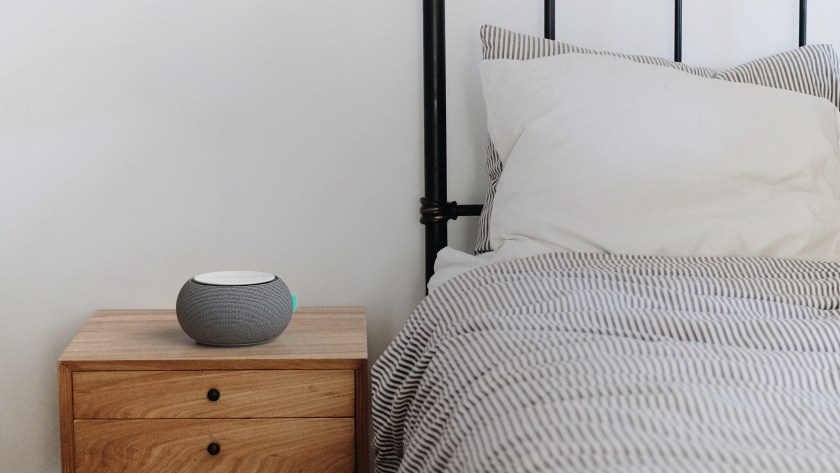 A SNOOZ portable white noise machine sits on a nightstand next to an empty bed