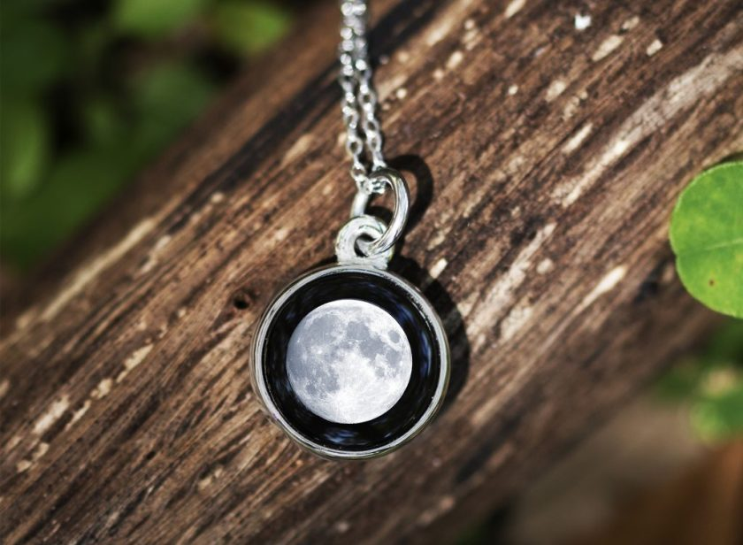 A full moon is depicted on a silver necklace from Moonglow jewelry