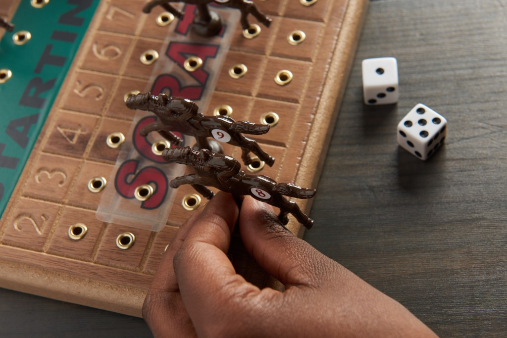 A person is seen playing a wooden tabletop horseracing game from Across The Board