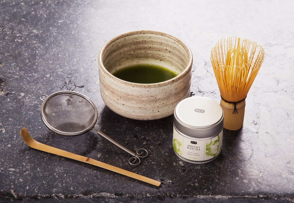 A fresh matcha tea set from P & T sits next to a cup of brewed matcha