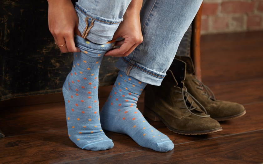 A woman is seen pulling on a pair of light blue polka dot medium compression socks from Sockwell