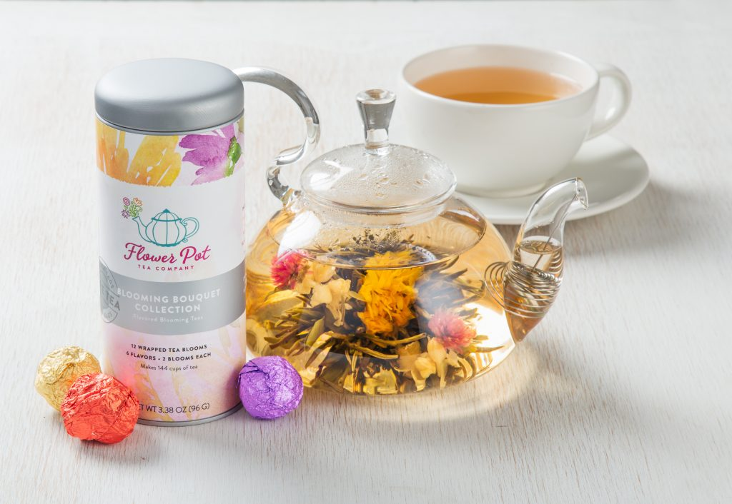 A clear tea pot filled with blowing tea flowers from The flower Pot Tea Company sits next to a canister of teas