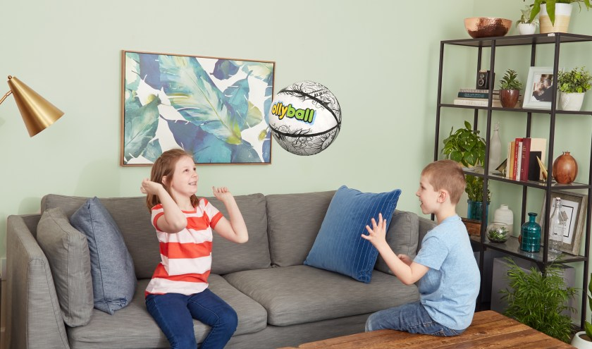 Two kids are seen tossing an  Ollyball inflatable indoor coloring ball in their living room