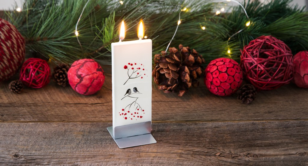 A holiday hand-painted Flatyz flat candle sits burning on a festive mantle