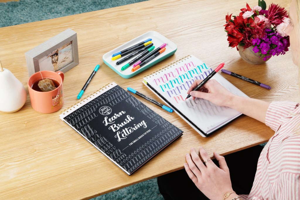 A woman is seen using a Kelly Creates workbook to practice calligraphy